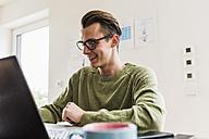 Smiling man at desk with laptop - UUF007834