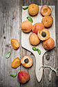 Sliced and whole organic apricots on wooden board - CZF000257