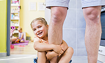 Daughter sitting on floor, holding onto father's leg - HAPF000508