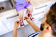 Father putting his daughter shoes on - HAPF000520