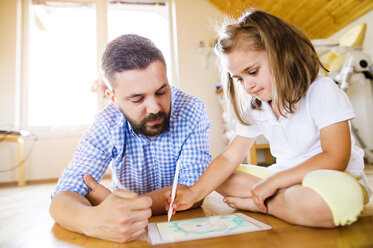 Father and daughter lying on floor, drawing on digital tablet - HAPF000538