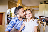 Father kissing his little daughter in kitchen - HAPF000541