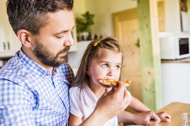 Father feeding his little daughter with pizza - HAPF000544