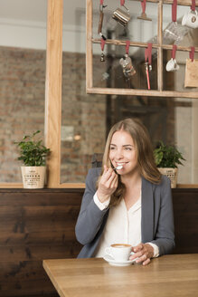 Portrait of smiling young woman tasting cappuccino in a coffee shop - KAF000156