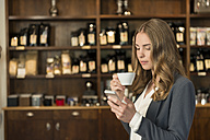 Young woman drinking coffee in a coffee shop looking at her smartphone - KAF000162