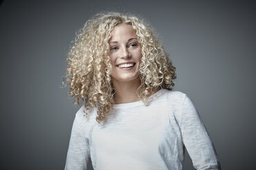 Portrait of happy blond woman with curly hair - RHF001663
