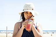 Young woman drinking cocktail on the beach - VABF000641