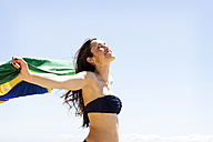 Young brunette woman playing with Brazilian flag at the beach - VABF000644
