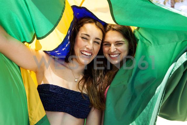Two friends wearing beachwear playing with Brazilian flag - VABF000647