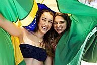 Two friends wearing beachwear playing with Brazilian flag - VABF000647