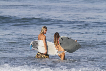 Indonesia, Bali, Surfer couple going into water - KNTF000401