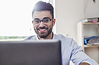 Smiling businessman with laptop in office - UUF007884