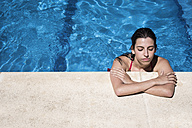 Portrait of a woman with closed eyes in a swimming pool relaxing at the edge - ABZF000747