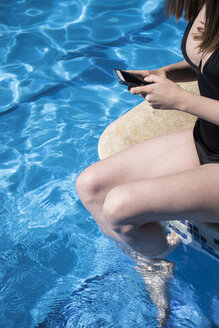 Woman sitting on the edge of a pool refreshing with her legs into the water using her phone, partial view - ABZF000750