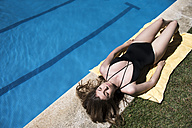 Woman in swimsuit lying on a towel sunbathing at pool edge - ABZF000753