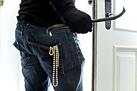 Burglar with pearl necklace in pocket leaving house - MAEF011866