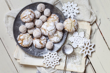 Home-baked Christmas cookies with powdered sugar on old book - SBDF002969