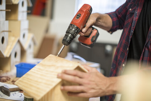 Man working with electric drill on birdhouse in workshop - ZEF008808