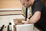 Man assembling furniture at home - RAEF001242