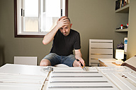 Man assembling furniture at home, looking desperate - RAEF001245