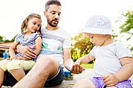 Father and his little daughters together in a park - HAPF000549