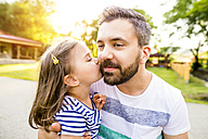 Little girl kissing father on his cheek in the park - HAPF000552