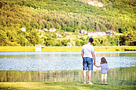 Back view of father and his little daughter standing at water's edge - HAPF000555