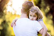 Portrait of sad little girl on father's arms - HAPF000567