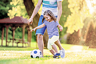 Happy little girl playing soccer with her father in a park - HAPF000570