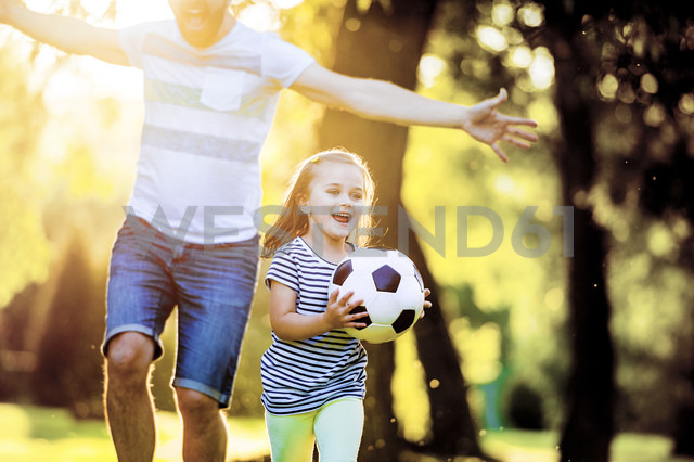 Happy little girl with soccer ball playing with her father in a park - HAPF000573