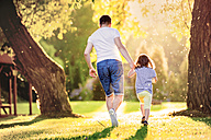 Back view of father and his little daughter running on a meadow in the park - HAPF000576