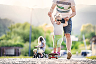 Father and his little daughter having fun with skateboard - HAPF000585
