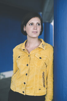 Portrait of woman wearing yellow jacket leaning against blue column - DASF000045