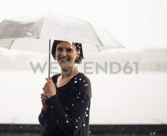 Portrait of smiling woman with umbrella on a rainy day - DASF000051