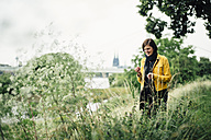 Germany, Cologne, happy woman standing on a meadow - DASF000054