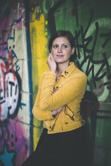 Portrait of young woman wearing yellow jacket standing in front of graffiti - DASF000057
