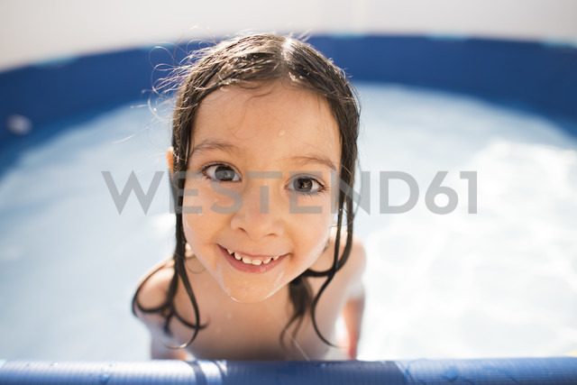 Portrait of smiling little girl in a paddling pool - JASF000857
