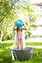 Little girl standing in a tub on a meadow pouring water on herself - LVF005052