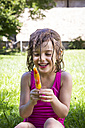 Portrait of happy little girl with wet hair sitting on a meadow with ice lolly - LVF005055