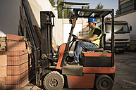 Construction worker working in the cart forklift - JASF000864