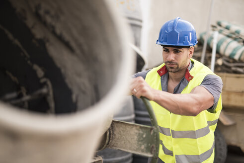 Construction worker next to the concrete mixer - JASF000876