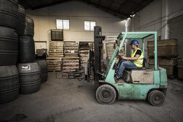 Worker inside cabin lift machine, barrels - JASF000894