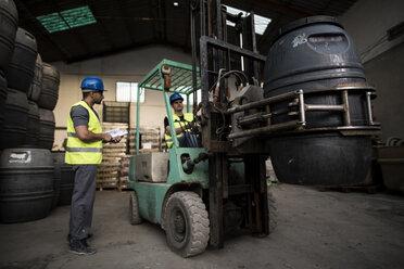 Worker inside cabin lift machine, barrels - JASF000900