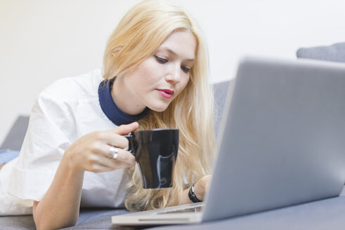 Blond young woman lying on couch with cup of coffee looking at laptop - FMOF000041