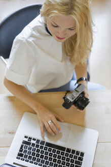 Blond woman with camera sitting at desk using laptop - FMOF000047