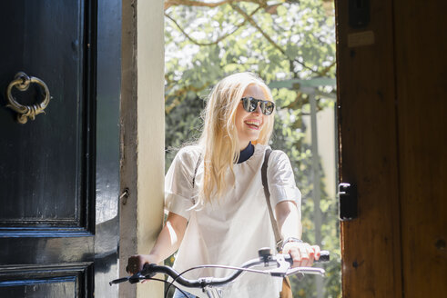 Portrait of laughing blond woman with bicycle standing at opened entrance door - FMOF000050