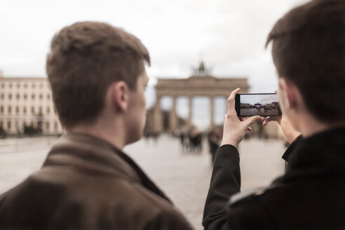 Two teenagers taking a smartphone image of the Brandenburg Gate in Berlin - MMFF001282