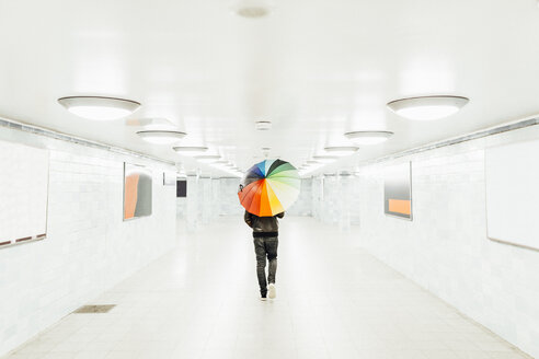 Man with colorful umbrella walking through an empty subway tunnel in Berlin - MMF001285