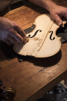 Luthier using a mini hand plane on the top plate of a violin in his workshop - ABZF000776