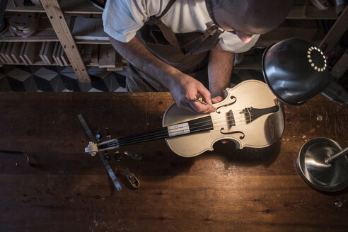 Luthier adjusting the sound post of an unvarnished violin in his workshop - ABZF000785